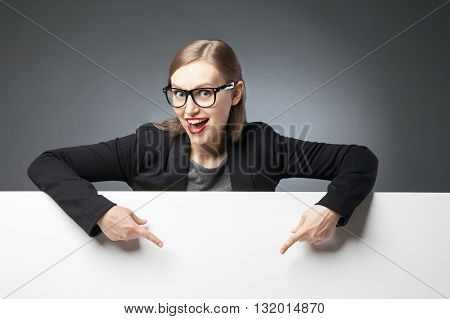 Portrait of beautiful lady in glasses pointing at blank space with index fingers