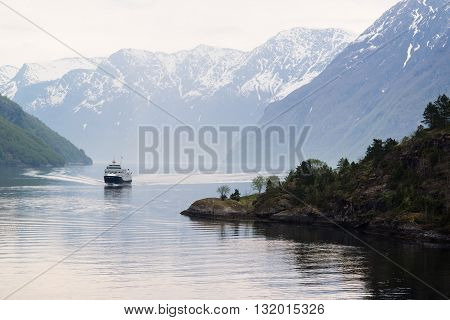 Ship approaching Geiranger on the Geirangerfjord in the early morning.