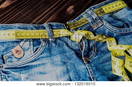 Jeans and measuring subject for weight loss on wooden background