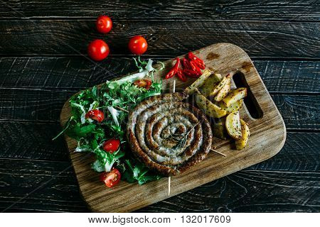 Tasty dinner grilled sausage and potatoes baked potato sausages with beer salad with baked potatoes and sausage salad on a wooden board
