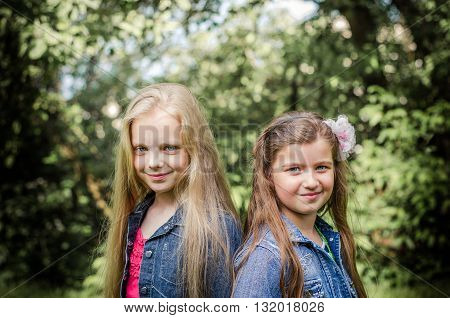 Portrait of two long haired preteen girls while smiling.