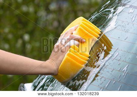 hand washing window of car with sponge