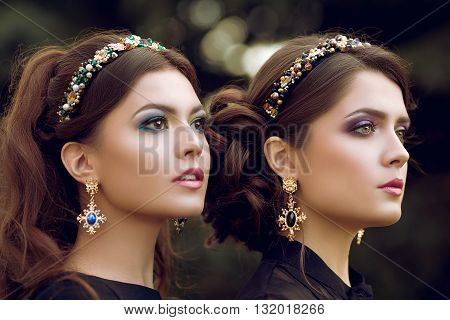 Two beautiful brunette women with a bright color makeup, jewelry, ring, earring. Close-up portrait of two girls with curly hair, hairstyles.