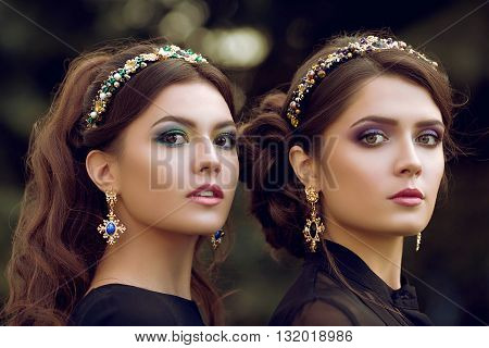 Close-up portrait of life image of two young beautiful women. Edgy, stylish jewelry, fashionable, trendy makeup, gold earrings with stones Hoop on the head with precious stones