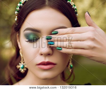 Portrait of beautiful woman, makeup and manicure in the same style, jewelry with precious stones. Makeup and manicure green, emerald