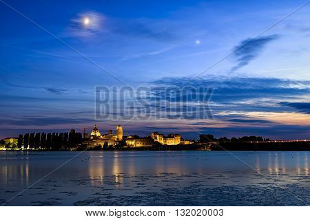 Mantua, Italy - June 21, 2015: Mantua night skyline on river with moon