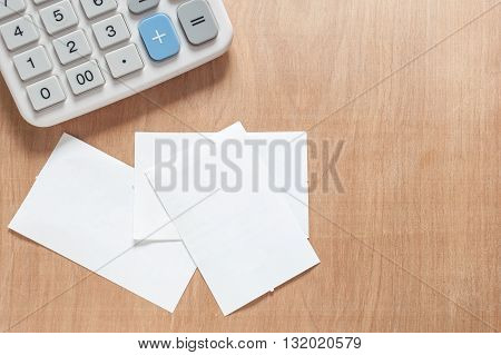 Bill and calculator on a wooden table