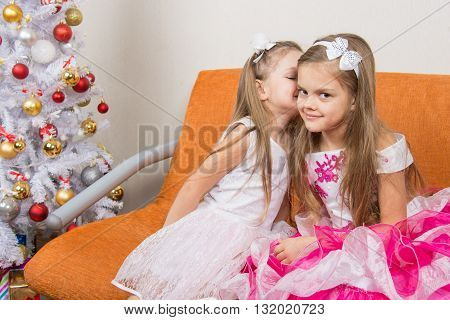Two Girls In Beautiful Dresses Whispering Sitting On Couch At Christmas Tree