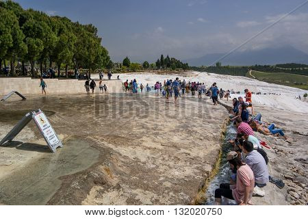 Pammukale Turkey - April 26 2015: People enjoy the thermal waters of white travertine. Travertine - a Calcium deposits.