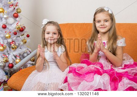 Two Girls In Beautiful Dresses Guessing Gifts For The New Year