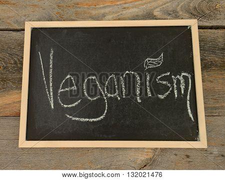 veganism written in chalk on a chalkboard on a rustic background