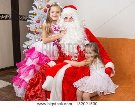 Two Girls In Beautiful Dresses Hug Santa Claus Sitting On A Couch