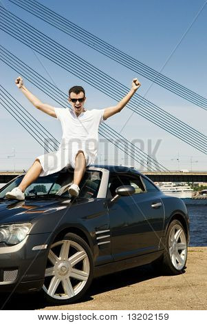 Happy young man sitting on top of his modern sport car