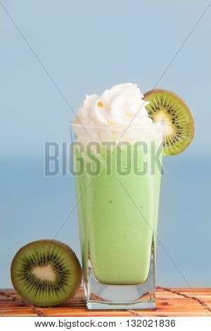 Kiwi smoothie set with sliced kiwi with sea on background. Cocktail made with kiwi and cream. Milkshake with fresh kiwi.