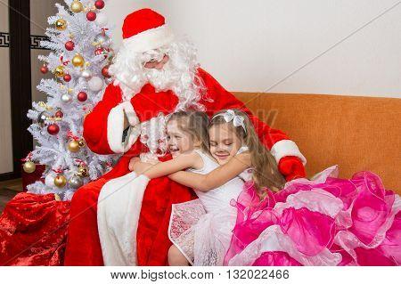 Two Girls In Beautiful Dresses Hug Santa Claus