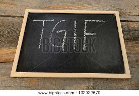Thank god it's friday - TGIF - written in chalk on a chalkboard on a rustic background