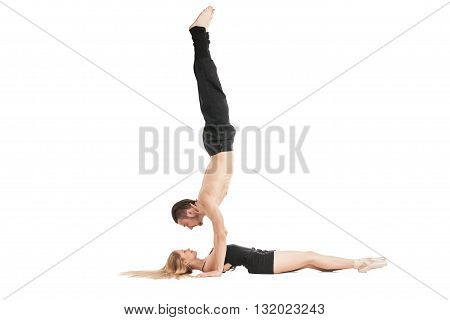 Gymnast in handstand above woman lying on floor.Isolated
