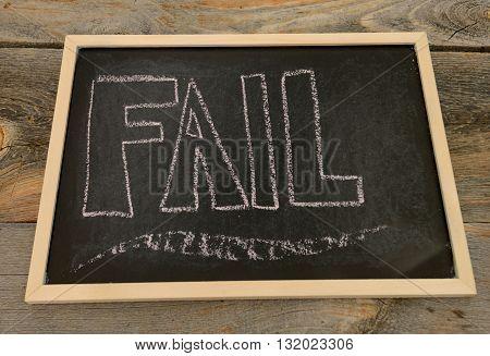 fail written in chalk on a chalkboard on a rustic background