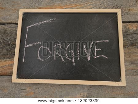 Forgive concept written in chalk on a chalkboard on a rustic background