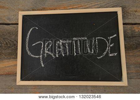Gratitude written in chalk on a chalkboard on a rustic background