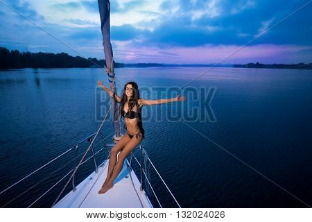 Girl with wineglass on yacht. Smiling lady with outstretched arms. So happy to be here. Amidst the ocean.