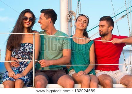 Women and men on yacht. Young people sit and smile. Last year's vacation was great. Clear sky and friendly talk.