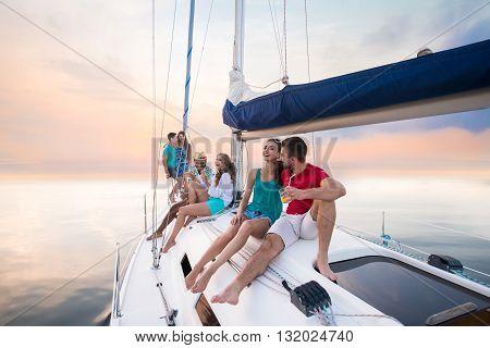 Young people sitting on yacht. Guys and girls laughing. Laughter prolongs life. Happy and healthy youth.