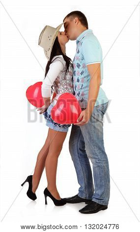 Young couple embraces, kisses and holds balloons - hearts isolated on the white background