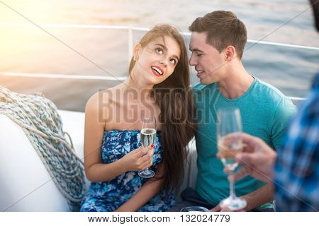 Girl with wineglass and guy. Young couple sitting on yacht. Sweet moments of romance. Head in the clouds.