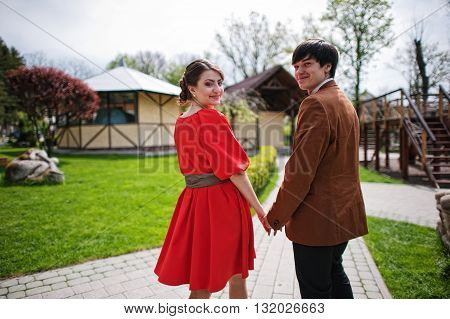 Back View Of Couple Holding Hands. Stylish Man At Velvet Jacket And Girl In Red Dress In Love Togeth