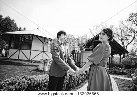 Couple Holding Hands. Stylish Man At Velvet Jacket And Girl In Red Dress In Love Together.  Black An