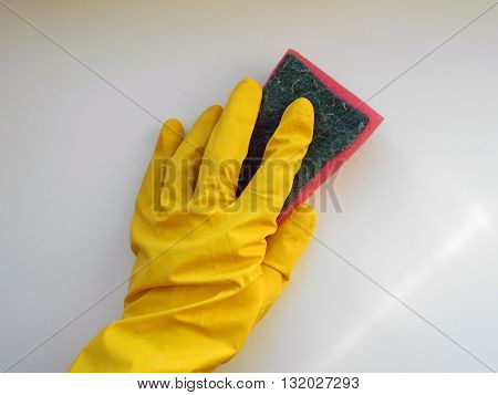 Hand in rubber glove holds a sponge to wash the surface. The glove protects hands skin against chemical effects of detergents.
