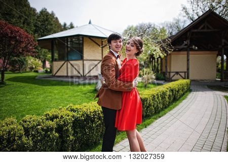 Couple Hugging And Laughing On Camera. Stylish Man At Velvet Jacket And Girl In Red Dress In Love To