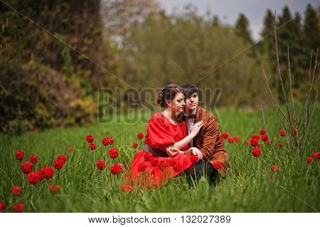 Couple Hugging In Love At Red Tulip Field. Stylish Man At Velvet Jacket And Girl In Red Dress In Lov