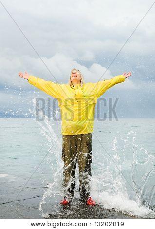 Feliz joven cerca del mar en la tormenta