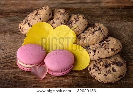 cookies and pink macaron with yellow leaves on wood