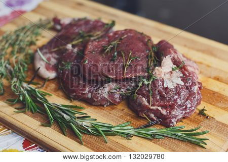 Fresh beef steak ready for BBQ cooking. Raw meat on a cutting board with rosemary leaf. Raw beef, veal meat on wood, closeup. Marinated in spices raw steak for barbecue.