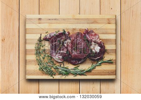 Fresh beef steak ready for BBQ cooking. Raw meat on a cutting board with rosemary leaf top view at wood. Raw beef, veal meat on wood, closeup. Marinated in spices raw steak for barbecue.