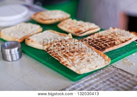 Grilled slices of bread for panini on the green stand.