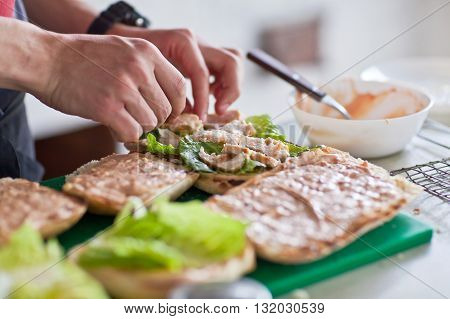 Cook lays out the pieces of herbs and chicken on toast for a panini.