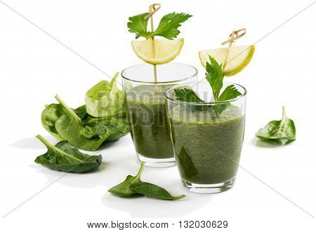 Vegetable smoothie of spinach with lemon in a glasses isolated on white background.