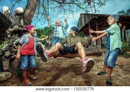 Happy boys pushing father on swing in playground