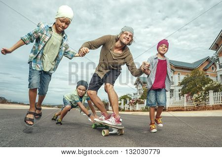Father learning to ride skateboard as young boys him in the suburb street having fun