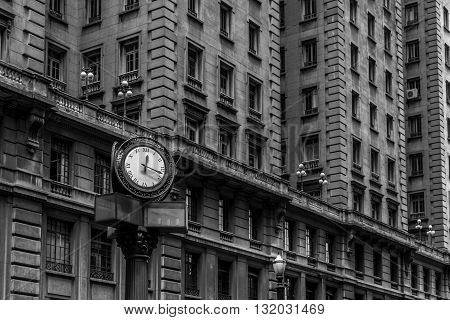 Black and white iconic old style street clock in front of buildings with windows with old street lamp posts in downtown area of São Paulo Brazil one of the biggest cities in the world.