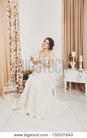 Wedding dress fashion. Beautiful young bride in vintage, shabby chic white wedding dress opens present in decorated box. Rustic wedding dress at model, in beautiful interior, studio shot, high key.