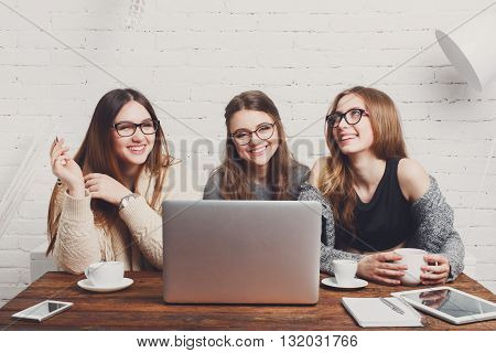 Portrait of three laughing girlfriends with laptop. Young girls friends happy together with computer. Women  friendship, modern life, gossip and internet dating concept. Technology and people.