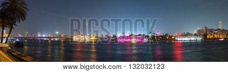 Cairo Egypt - May 26 2016: Wide panoramic view of the Island of Zamalek in central Cairo at night with it's famous boat restaurants on the Nile river.