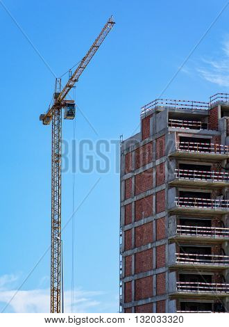 Building Crane and Building Under Construction on blue sky background
