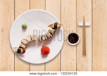 Japanese food restaurant, sushi maki gunkan unagi roll plate or platter set. Set for two with chopsticks, ginger, soy, wasabi. Eel Sushi at black stone and wood planks background. Top view, flat lay.