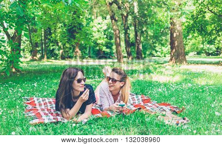 Two young women lying down on grass